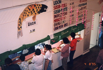 A photo from above showing people lined up at church kitchen serving counter. There is a large koi fish painting on the wall above the counter, and beside it a menu of many Japanese food offerings and prices. There is a digital camera date stamp in the lower right corner that reads 4 8 '95