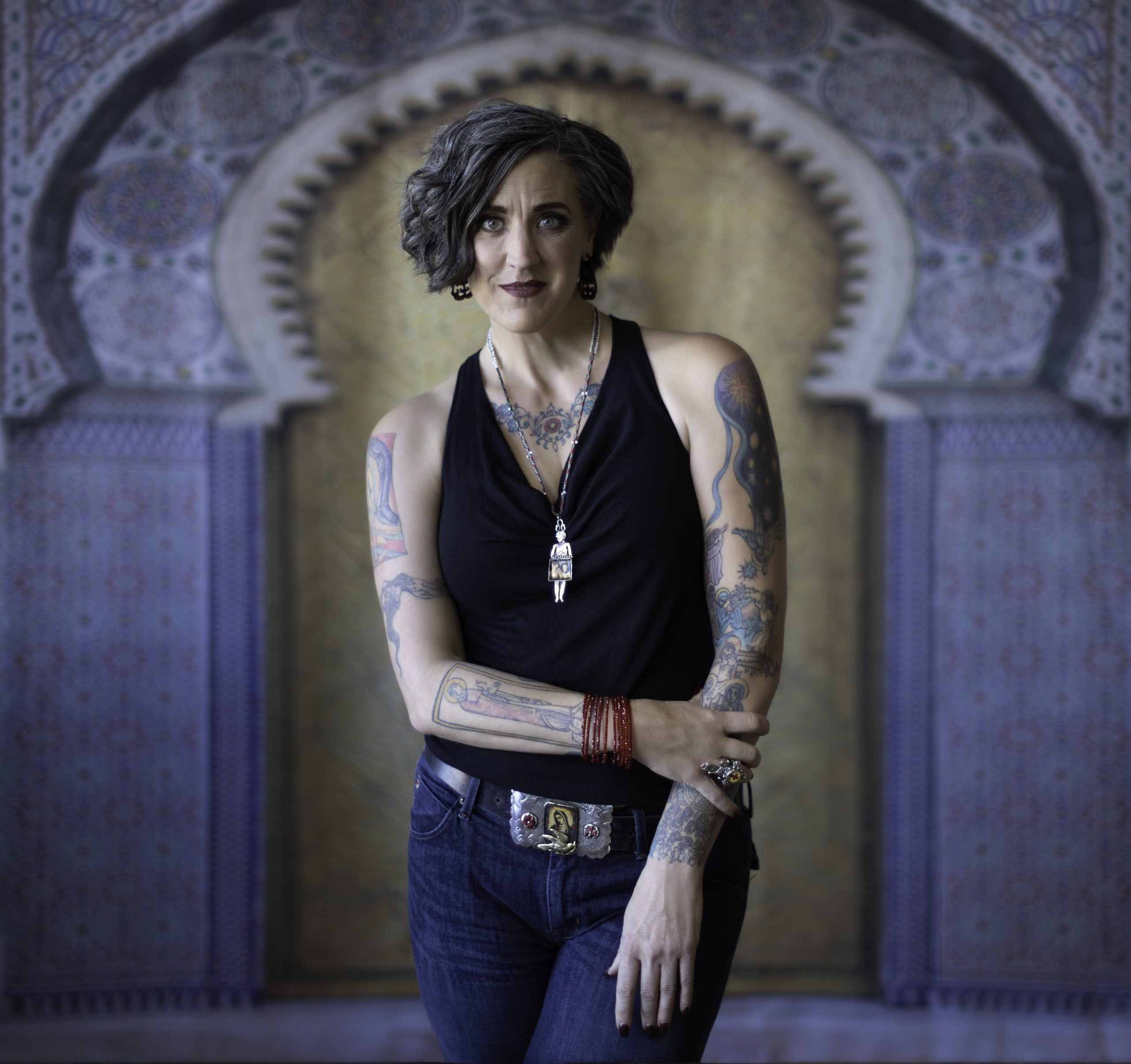 Person with asymmetrical curly bob hairstyle wearing a black sleeveless v-neck shirt, tattooed arms, one crossing her body and holding the other, in blue jeans with a belt that has a large silver belt buckle. She's wearing a silver necklace and standing in front of a gold and stone Moorish arch.