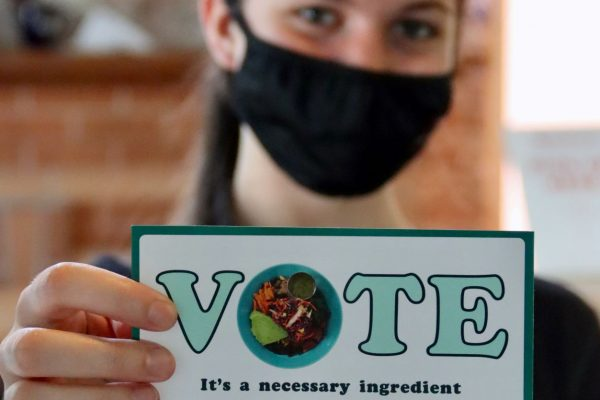 Person wearing a face mask holding out a small sign that reads Vote It's A Necessary Ingredient