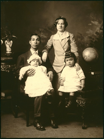 Very old sepia tone photo of an Asian man wearing a suit and holding a baby on his lap. The baby is dressed in a long white dress and wearing a white bonnet. There is a woman standing beside him with her wrist resting on his shoulder. She is wearing a ladies suit of the era, with a skirt and a small black hat. In from of her is a toddler sitting on a chair, wearing a white tunic and small black cap. There is a plant in the background, a globe on a stand, and what looks to be a vase.